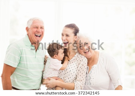 Happy grandparents playing with their grandson at home - stock photo