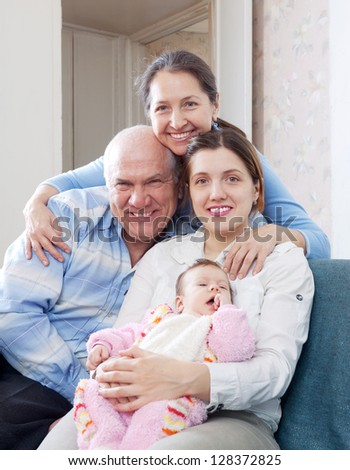 happy grandparents with daughter and granddaughter in home interior together - stock photo