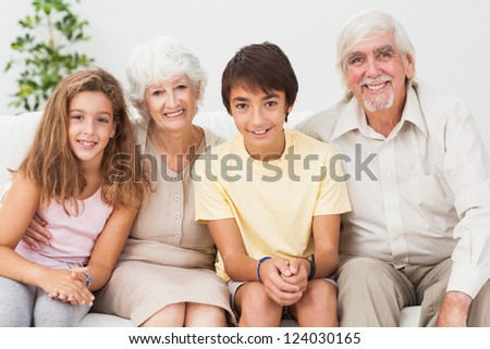 Happy grandparents with grandchilden on sofa