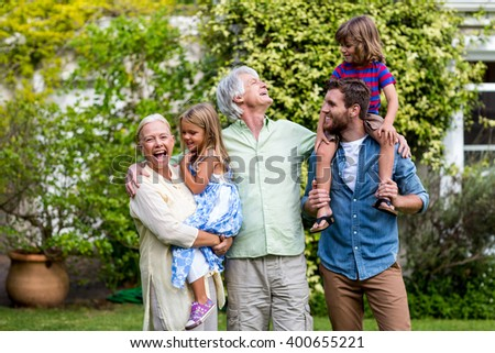 Happy grandparents with grandchildren and son standing in yard - stock photo