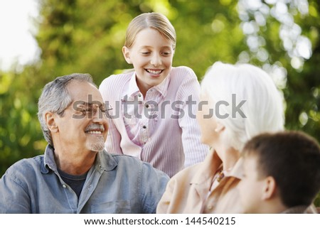 Happy grandparents with grandchildren in back yard - stock photo