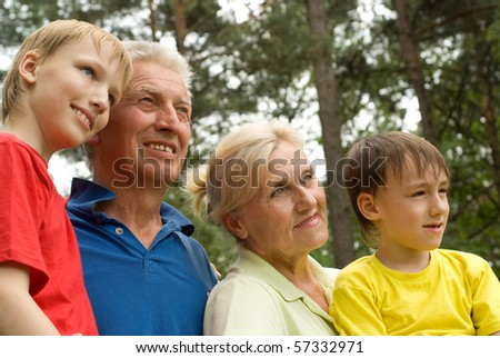 happy grandparents  with grandchildren in the forest