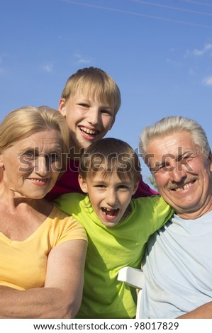 Happy grandparents with grandchildren with fool on the street - stock photo