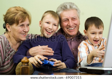 happy grandparents with their grandchildren play on the computer - stock photo