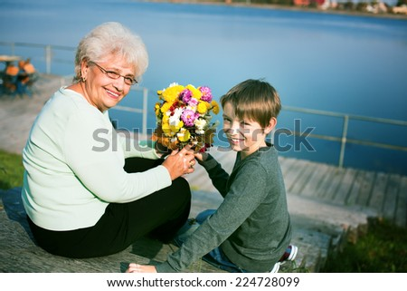 happy grandson giving flovers to grandmother outdoors - stock photo
