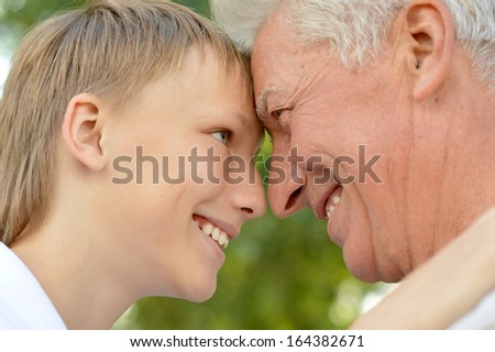 Happy grandson with grandfather at the nature