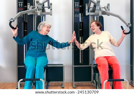 Happy Grannies Enjoying Chest Press Exercise, as if Playing, While Touching Their Palms and Looking Each Other. - stock photo
