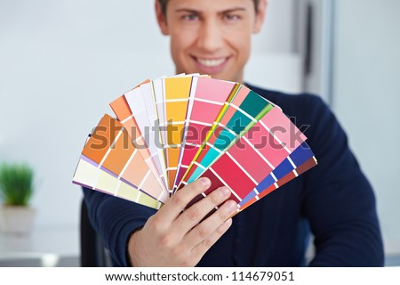 Happy graphic designer holding color fan in his hand - stock photo