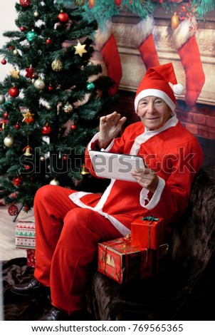 Happy gray haired elderly man dressed in Santa Claus costume holding digital tablet sitting near the Christmas tree in front of fireplace. Christmas concept.