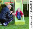 Happy great grandfather with his adorable granddaughter, cute toddler girl, playing on the slide in the garden at backyard of the house on a sunny day. Selective focus on child. - stock photo