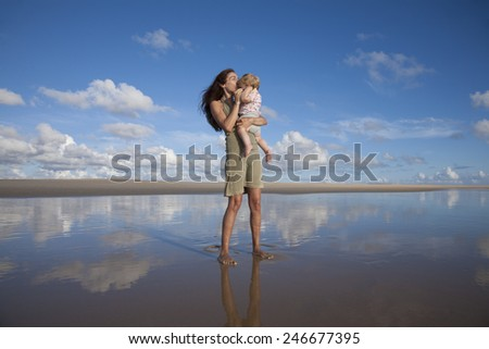 happy green dress woman with sunglasses kiss one year blonde baby in her arms at beach Conil Cadiz Spain - stock photo
