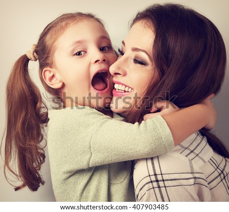 Happy grimacing kid wanting to biting her laughing mother in nose with fun face. Vintage toned portrait - stock photo