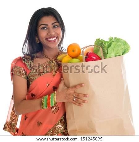 Happy grocery shopper. Portrait of beautiful traditional Indian woman in sari dress holding paper shopping bag full of groceries isolated on white. - stock photo