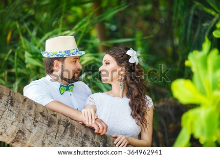 Happy groom and bride having fun in a tropical jungle under the palm tree. Wedding and honeymoon concept. - stock photo