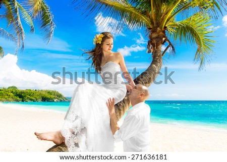 Happy groom and bride having fun on the sandy tropical beach under the palm tree. Wedding and honeymoon concept. - stock photo