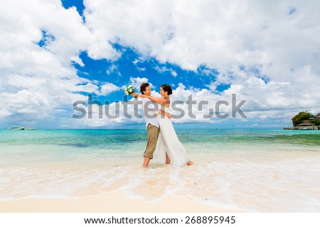 Happy groom and bride having fun on the sandy tropical beach. Wedding and honeymoon concept. - stock photo