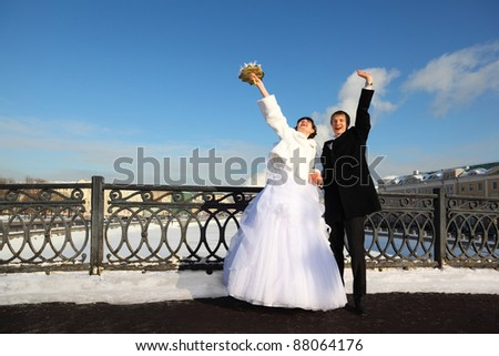 happy groom and bride shouting and waving their hands at winter outdoors, couple standing on bridge - stock photo