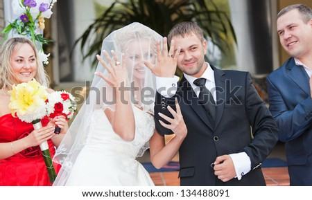Happy groom and the bride show wedding rings to guests - stock photo