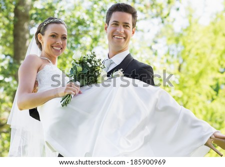 Happy groom carrying bride while looking away in garden - stock photo