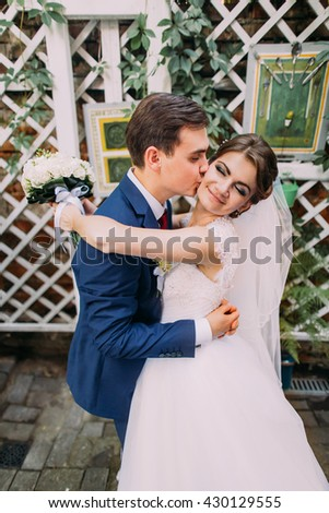 Happy groom embracing his new wife after their wedding ceremony. Close-up - stock photo