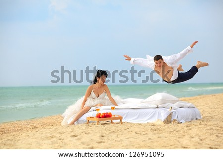 Happy groom flying on bed to his sweetheart on the beach - stock photo