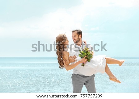 Happy groom holding bride in his arms on seashore