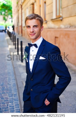 Happy groom is standing and posing alone