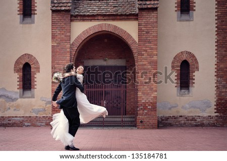 Happy groom spinning hir bride in front of a church - stock photo