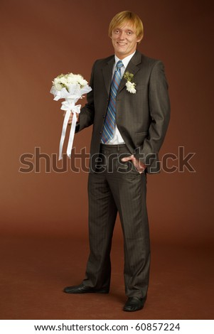 Happy groom with a bouquet on brown background - stock photo
