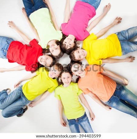 Happy group children isolated at white background. Smiling teen lying in a circle. Friendship boys and girls