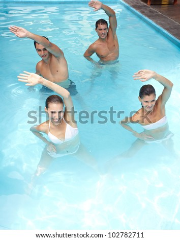 Happy group doing aqua fitness in swimming pool - stock photo