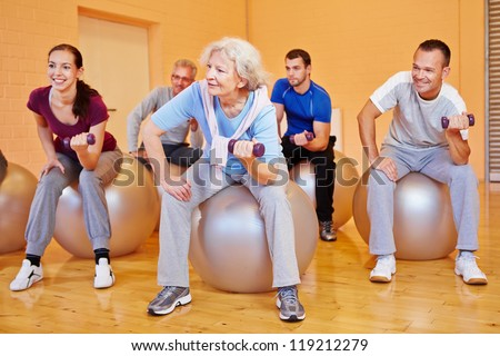 Happy group doing back training exercises in gym with dumbbells - stock photo