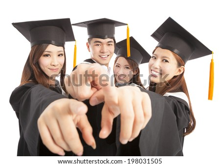 happy group graduate students point to the same direction - stock photo