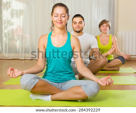 happy group having yoga class in sport club - stock photo