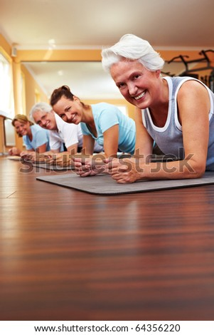 Happy group in a gym doing Pilates - stock photo