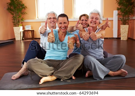 Happy group in a gym holding their thumbs up - stock photo