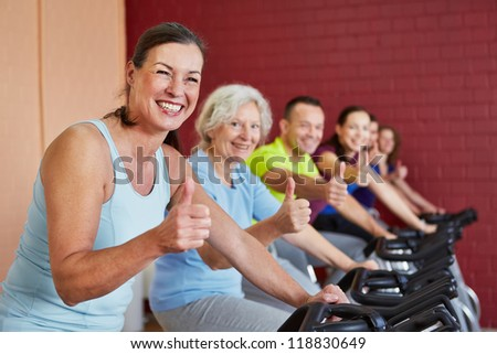 Happy group in fitness center in spinning class holding the thumbs up - stock photo