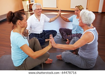 Happy group meditating in circle in a gym - stock photo