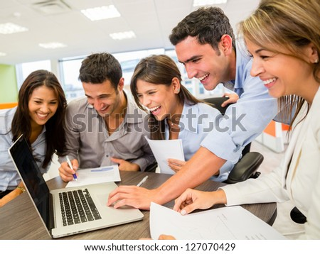 Happy group of business people looking at the computer - stock photo