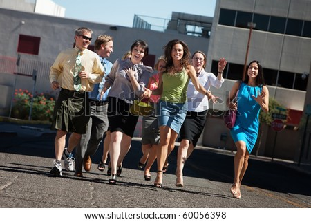 Happy group of business people running on city street - stock photo