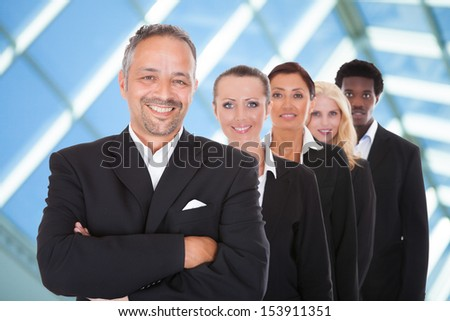 Happy Group Of Business People Standing In A Row Over Blue Background