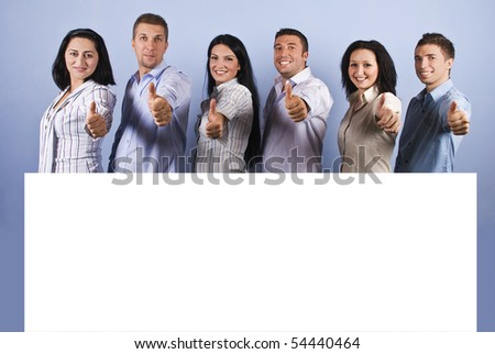 Happy group of business people with white blank banner giving thumbs up and smiling - stock photo