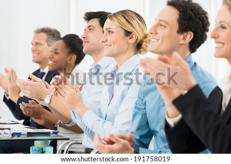 Happy Group Of Businesspeople Clapping In Boardroom - stock photo