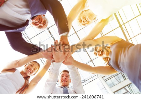 Happy group of businesspeople stacking their hands in cooperation - stock photo