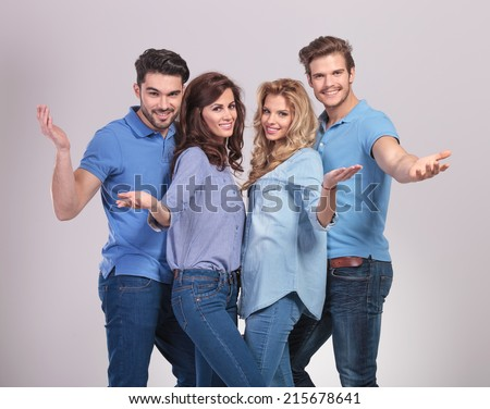 happy group of casual people welcoming and inviting to join the team on grey background - stock photo