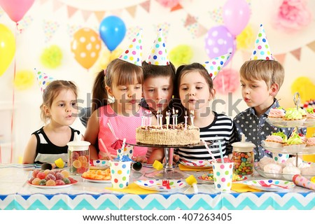 Happy group of children blowing candles on cake at birthday party