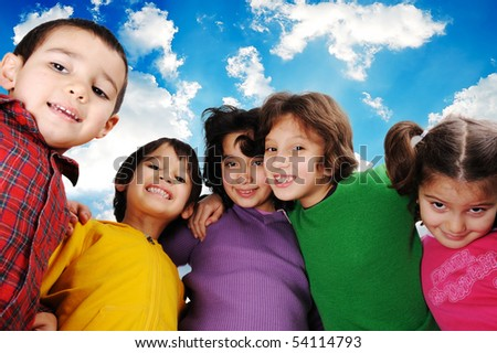 Happy group of children outdoor, beautiful sky behind them - stock photo