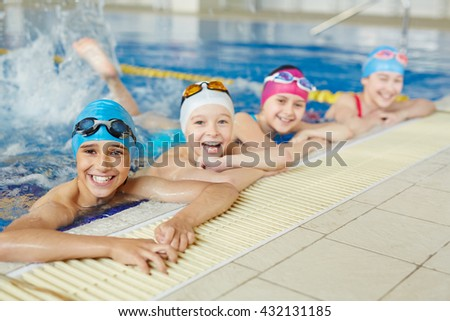 Happy group of children swimming together - stock photo