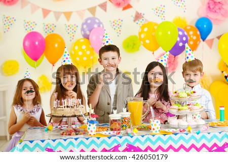 Happy group of children with paper  mustache having fun at birthday party