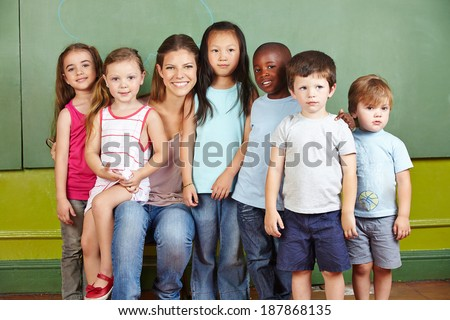 Happy group of children with smiling kindergarten teacher in a room - stock photo